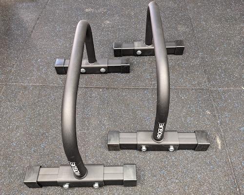 Black rogue bolt together parallettes on home gym floor