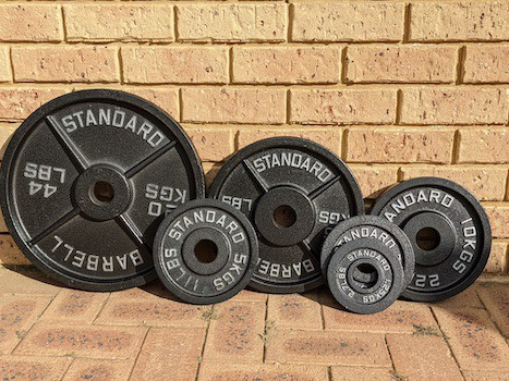 Rogue Fitness Olympic plates lined up against a wall