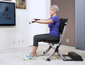 Older woman in purple shirt using a resistance chair for seniors