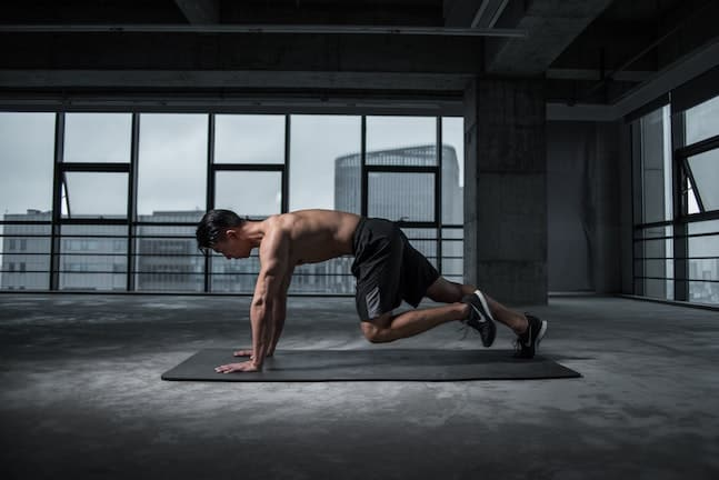 Man doing a home workout on the floor using one of the 11 best fitness apps to guide him