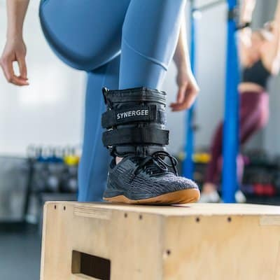 woman in blue pants wearing a black synergee adjustable ankle weight