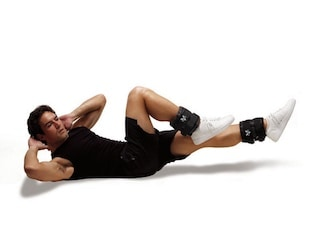 Man doing bicycle crunches while wearing Valeos adjustable ankle weights