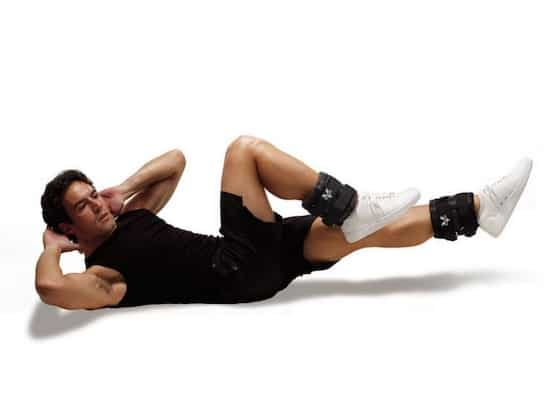 Man in black clothes working out while wearing Valeo adjustable ankle weights