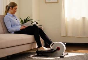 Woman sitting on couch reading while using a mini elliptical machine