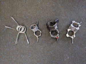 Multiple Olympic barbell collars on home gym floor