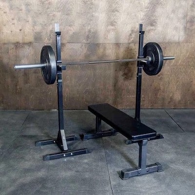 Fringe Sport indy squat racks with loaded barbell on j cups above black weight bench