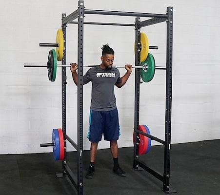 Man squatting in black titan fitness power rack