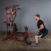 Man doing mid rows on the EXM1 home gym with leg press