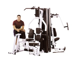 Man standing next to body-solid exm3000 home gym with leg press station