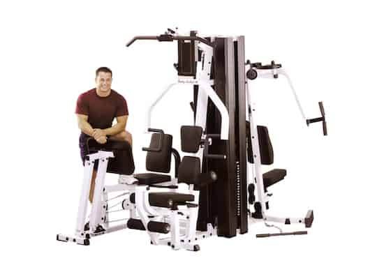 Man in red shirt standing next to EXM3000lps home gym