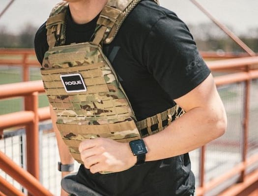 Man running with camo colored plate carrier over black t-shirt