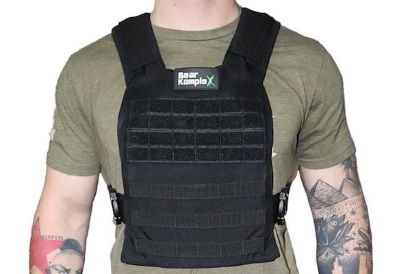 Man wearing black Bear Komplex weight vest over green t-shirt