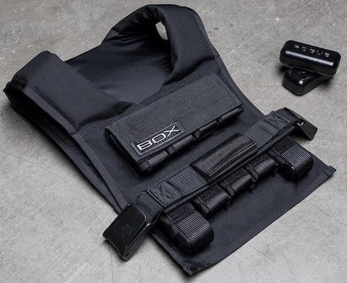 Black BOX weight vest for calisthenics lying on grey floor