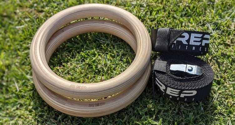 Rep Fitness wood gymnastic rings with straps lying on grass