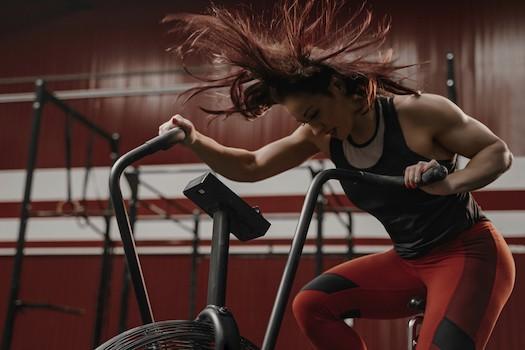 Woman doing high intensity interval on an air bike