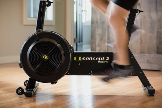 Man riding on concept2 bikeerg with legs blurring
