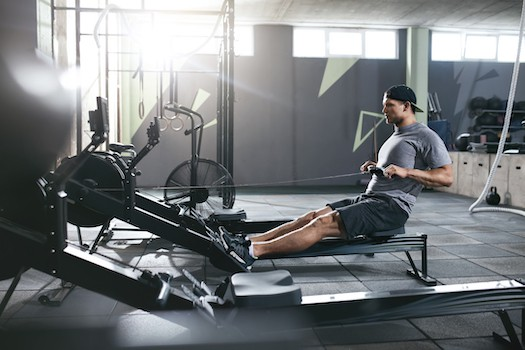 Man exercising on a rowing machine in a gym