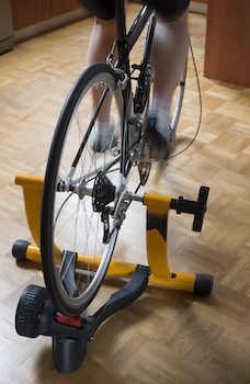 Woman using an indoor cycle trainer with a real road bike