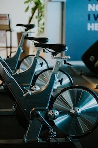 A row of spin bikes with flywheel at the back