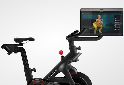 Peloton bike with touchscreen showing personal trainer