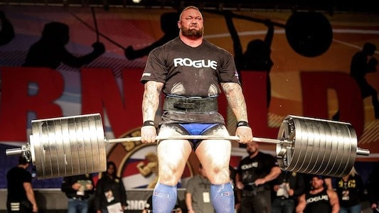 man lifting heavy barbell and barbell is bending to