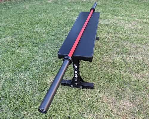 Red and black Cerkaote rogue ohio barbell for crossfit sitting on black bench in back garden