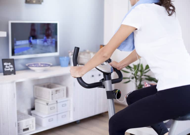 Woman riding best exercise bike under $300 in living room while watching tv