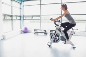 Woman riding a spinning bike in her home gym