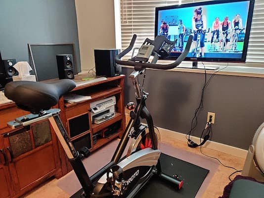 Joroto X2 spinning bike in home gym in front of large tv