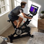 Man riding nordictrack studio cycle spin bike in his home gym watching the touchscreen