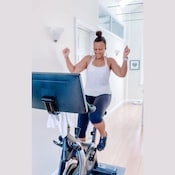 woman happily riding the soulcycle at home spin bike