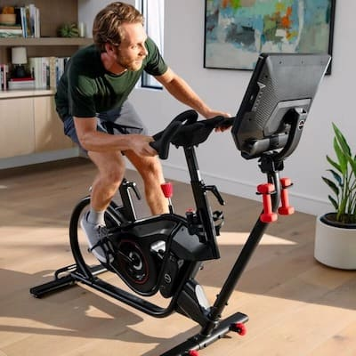 Man leaning and riding on a bowflex velocore spinning bike in his home gym