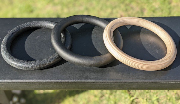Wood, metal, and plastic rings sitting on a black weight bench