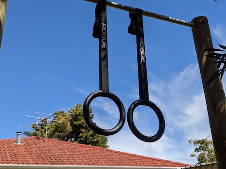Pair of Rogue Gymnastic rings hanging on pull-up bar in suburban backyard