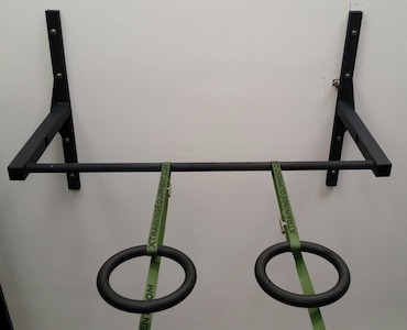 Gymnastic rings hanging from ceiling-mounted pull-up bar