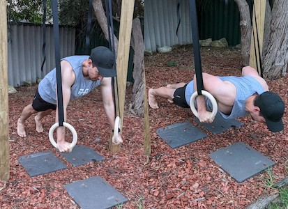 man doing push-up support hold on gymnastic rngs in back garden