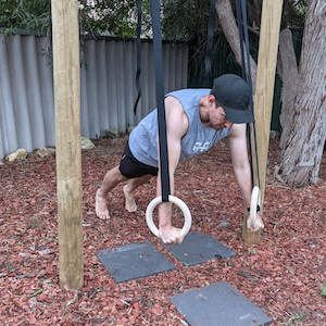 man doing push-up support hold on gymnastic rings in back garden