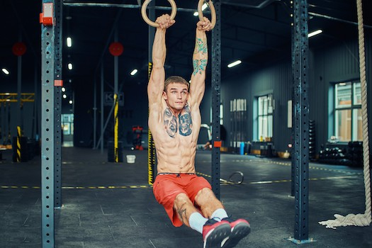 Man on gymnastic rings showing benefits to physique
