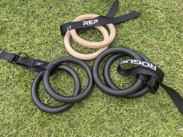 Pairs of wood, plastic, and metal gymnastics rings with straps on green grass