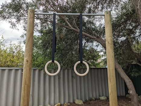 Pair of wood rings hanging from pull-up bar
