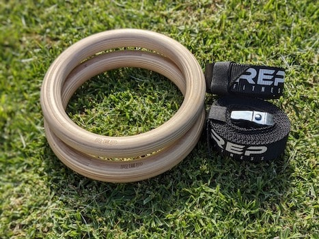 Rep fitness wood rings on grass with straps