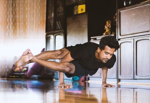 Man doing difficult yoga pose at home