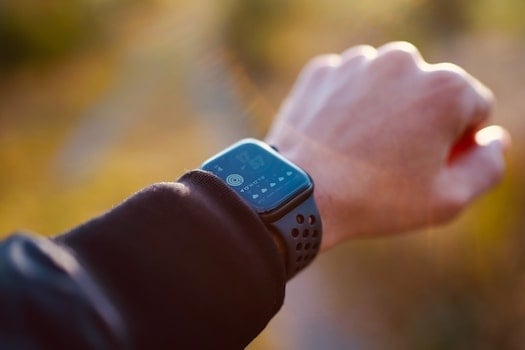 Person looking at fitness watch to get themselves motivated to workout at home