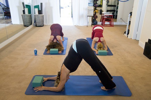 Three women doing yoga poses in a home gym
