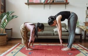 Mother and daughter showing ways to improve flexibility at home