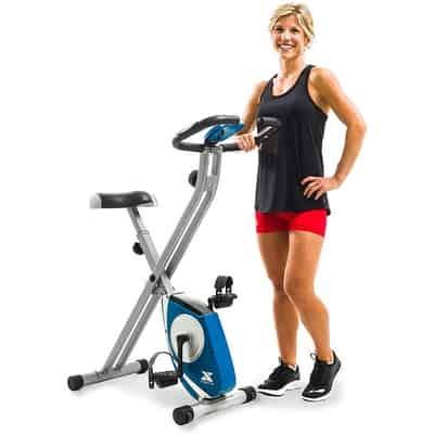 Woman standing next xterra fitness fb150 folding exercise bike