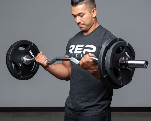 Man doing bicep curls with loaded Rep Fitness EZ curl bar